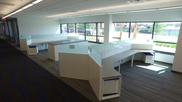 Desks in a polygon shape with panels in the middle to separate direct views of other employees in an open workspace.