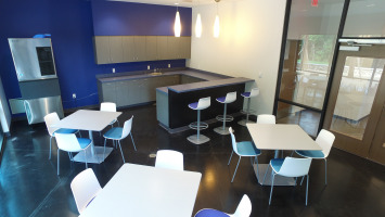 Blue and white walls with blue chairs and white tables in a work cafe.