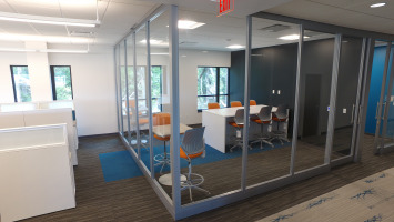 Glass panels create a square room with privacy from the remainder of an open workspace.