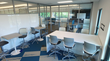 White desks and chairs with a wall whiteboard for written collaboration and brainstorming.