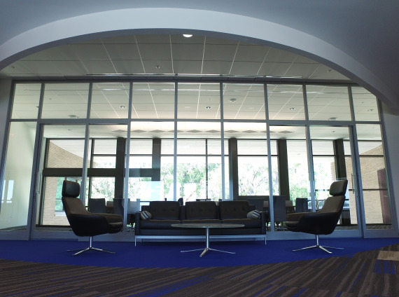 Front lobby with floor to ceiling windows and black lobby furniture at Info Tech, a Gainesville based company.