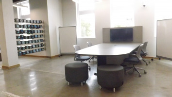 Stools with legs surround a table with a tv monitor for collaborative work.