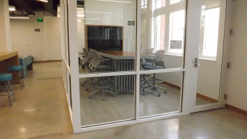 Glass privacy wall enclosing a media:scape table and tv monitor with four chairs surrounding the table
