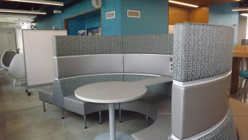 Coalesse lounge seating ganged together and arranged in a half circle with a platinum sold table extending through the middle of the half circle. Grey Steelcase Jenny chairs can be seen in the background