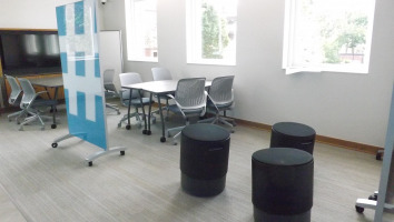 Three black Steelcase Buoy seats with a Clarus freestanding glassboard and two sets of fliptop tables and Steelcase Cobi chairs with platinum frames and grey seats.