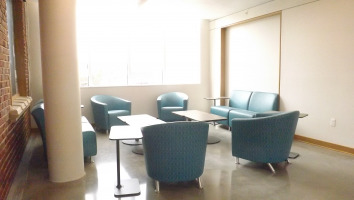 Jenny lounge seating by steelcase with two coffee tables, chairs colored in a teal greenish-blue.