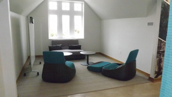 Lounge chairs on floor with two work/end tables for personal use