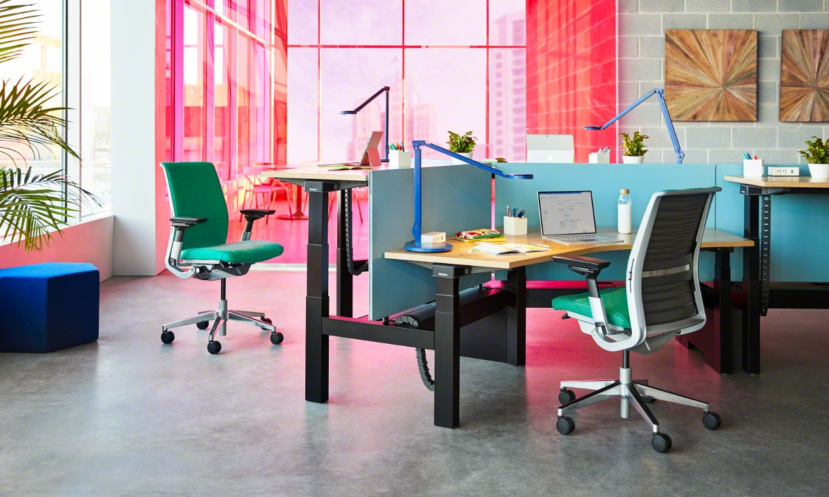 Pink hues with greens and blues in a lighted personal desk area with chairs and desk accessories