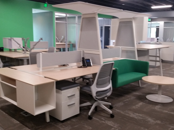 Group desking areas that have tall Turnstone Bivi standing unit. Green colored lobby furniture with blonde colored laminate for hotel desking.