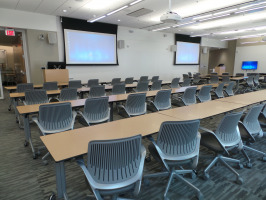 Rows of Cobi chairs in a classroom setting with two monitors at the front of the room.
