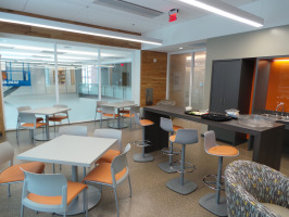 Orange Coalesse Enea stools in cafeteria area with three tables, deep mahogany counter top and multicolored lounge seating.
