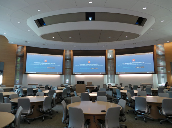 Three monitors on walls in front with multiple tables and chairs in conference extra large conference room with hundreds of task chairs and many blonde colored round conference tables.