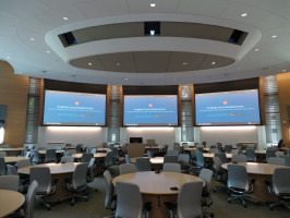 Three monitors on walls in front with multiple tables and chairs in conference extra large conference room.