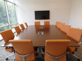 Conference room with long table equipped with digital inputs/outputs, cherry laminate conference table with twelve orange conference chairs and a multimedia television for conferencing.