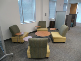 Lounge seating with tablet arms for laptop accessibility. Lounge furniture is mustard yellow seats with green backs.