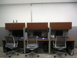 Black Steelcase Think chairs with cherry colored laminate call center desking with cubicle partitions.