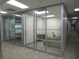 Privacy walls creating separated office space with a guest chair, a task chair, a desk and a storage cabinet.
