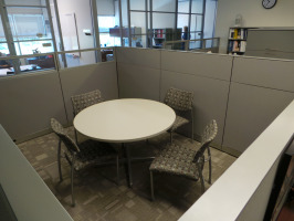 Private meeting space with a white table and four multicolored guest chairs inside of a cubicle separated space.
