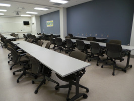 Conference room seating with white flip-top tables and black task seating throughout the entire room