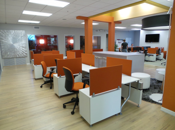 Hotel desking with orange chairs and orange privacy screens with white ottomans in a central lobby location