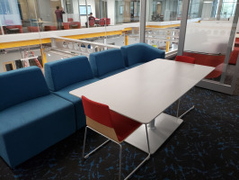 White rectangle lounge table with red chairs and blue lounge seating.