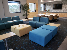 Various shades of blue lobby seaing with beige ottomans and blonde laminate end tables. White round conference table in background with eight beige conference chairs.
