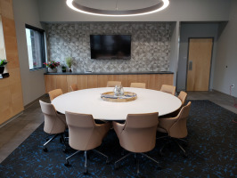 White roundtable meeting space with beige conference chairs. Room designed with geometric designs and brown and black colors.