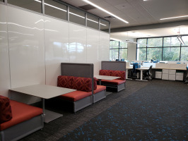 White Steelcase markerboard privacy walls on the left with black Coalesse Lagunitas lounge seating with red cushions. Hotel desking with blue chairs can be seen in the background.