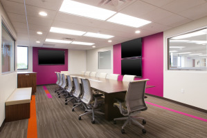 Hot pink accent walls with long cherry laminate conference table and white executive Steelcase Think chairs.