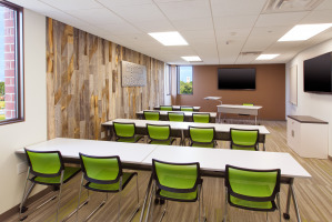 Wood grain carpet and accent wall with green guest chairs and white flip top tables for training sessions.