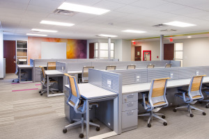 Yellow Steelcase Think chairs at grey hotel desking with metal pedestals for support.