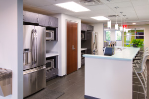Cafeteria with stainless steel appliances, cherry laminate storage door, white stools at the white and blue counter top.