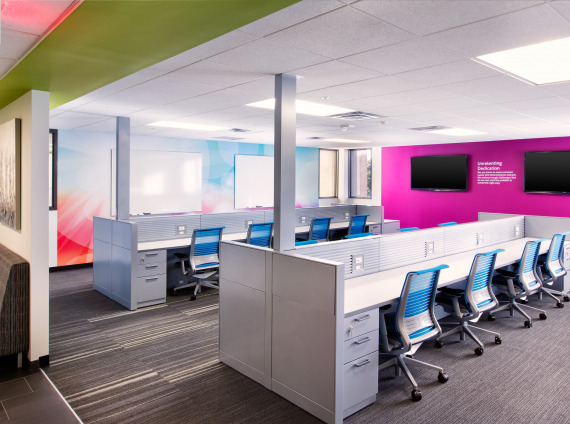 Bold pink accent wall with blue Steelcase Think chairs and white hotel desking with storage pedestals