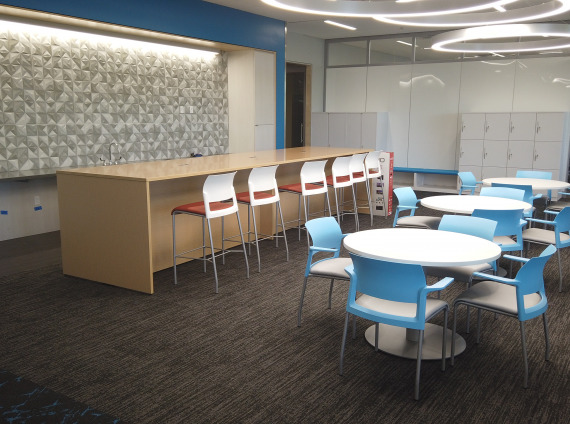 Cafeteria and meeting area with white tables, blue chairs, red stools, and a blonde laminate colored counter space.