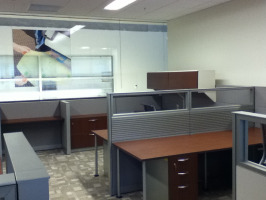 Cubicle desking with glass stackers on top of pabels, with cherry laminate desking and filing cabinet under desk.