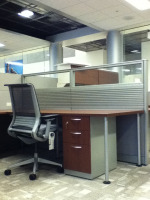 Cubicle desk with glass stackers on top of panels, a cherry colored laminate desk and a Steelcase Leap chair with a file cabinet under the desk.