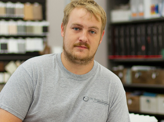 Male with blonde hair posing in grey tshirt for headshot.