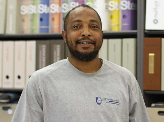 Male installer wearing grey tshirt with OEC logo while posing for headshot.