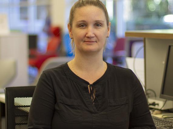 Female sales administrator wearing black shirt posing for headshot.