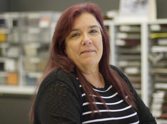 Female designer wearing black and white striped long sleeved shirt posing for head shot.