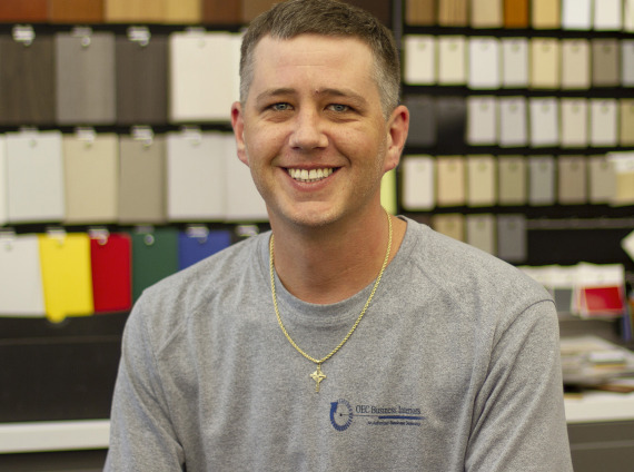 Male warehouse technician wearing grey tshirt as he poses for head shot.