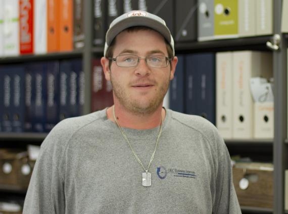 Male installer wearing grey baseball cap and shirt while posing for headshot.