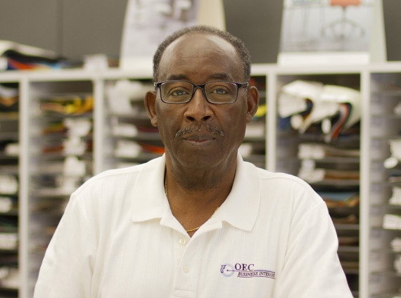 Male installer wear glasses and white polo shirt with OEC logo while posing for headshot.