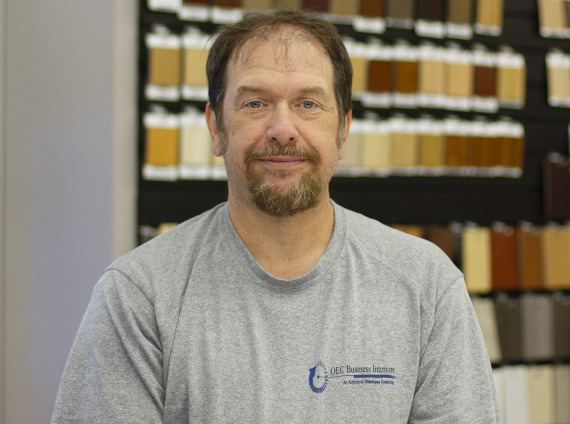 Male warehouse technician wearing grey tshirt with OEC logo for headshot.