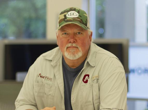 Male service repairman wearing camoflauge baseball cap and khaki fishing shirt.