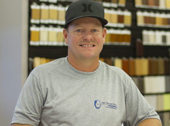 Male installer wearing black baseball cap and grey tshirt while posing for head shot.