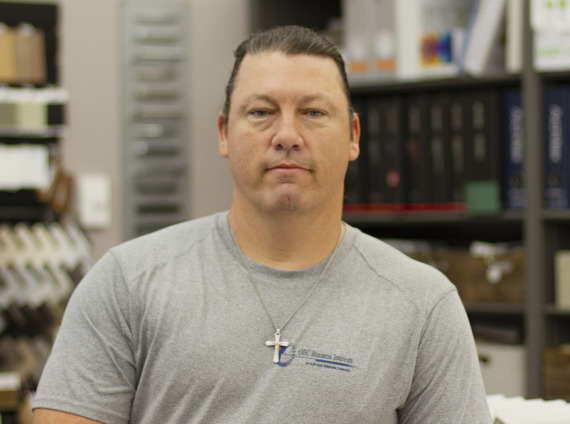 Male installer with black hair and cross necklace posing for head shot while wearing grey tshirt.