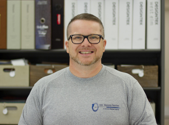 Warehouse manager smiling with glasses on wearing a grey tshirt while posing for head shot.