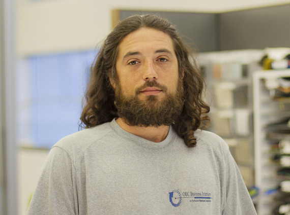 Male installer with long brown hair posing for headshot while wearing grey tshirt