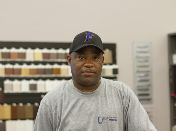 Male installer wearing University of Florida baseball cap and wearing grey tshirt while posing for head shot.